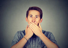Scared young man covering mouth with hands Stock Photos