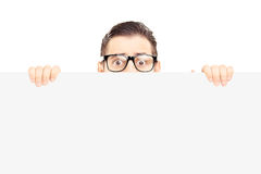 Scared young man with glasses hiding behind a blank panel Stock Photography