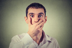 Scared young man with hand over his mouth, stunned and speechless Royalty Free Stock Image