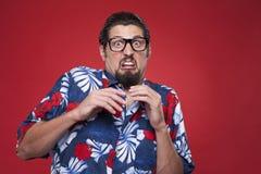 Scared young man in Hawaiian shirt looking at camera Royalty Free Stock Images