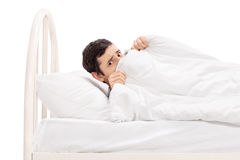 Scared young man hiding under a blanket. Studio shot of a scared young man hiding under a blanket and lying in bed isolated on white background Stock Images