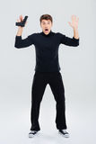 Scared young man holding gun and standing with hands up Royalty Free Stock Photo