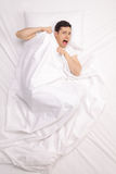 Scared young man laying in bed. Vertical top view shot of a scared young man laying in bed covered with blanket and screaming Stock Photo