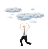 Scared young man protecting from falling clouds with his hands Royalty Free Stock Image