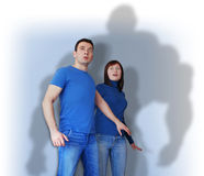 Scared young man and woman in blue wear. Shocked and scared young man and woman in blue wear. They are afraid of the terrible shadow Royalty Free Stock Image