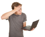 Scared young man working on laptop Royalty Free Stock Image