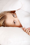 Scared young woman. In bed Stock Photos