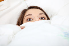 Scared young woman. In bed Royalty Free Stock Photos