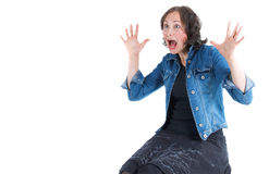 Scared young woman. An attracctive young woman with brown hair wearing jeans jacket and black skirt, is screaming in surprise or fear, holding her hands up royalty free stock image