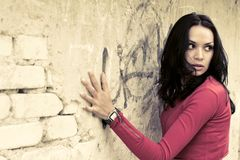 Scared young woman. Near the brick wall Stock Photo