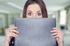 Scared young woman. Standing behind a folder in her office Stock Photo