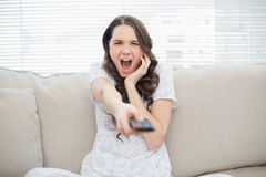 Scared young woman changing tv station Stock Photo