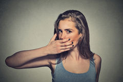 Scared young woman covering with hand her mouth Royalty Free Stock Photos