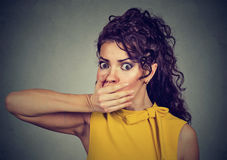 Scared young woman covering with hand her mouth Stock Photography