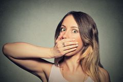 Scared young woman covering with hand her mouth Stock Photos