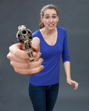 Scared young woman with gun expressing anxiety for self-defense Stock Image