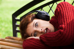 Scared young woman listening to music. Stock Photo