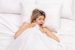 Scared young woman lying in bed stock image