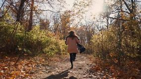 Scared young woman is running on path in autumn forest in daytime, back view. Frightened brunette girl is fleeing in woodland in sunny day. Back view of her stock video footage