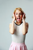 Scared young woman shouting. On gray background Royalty Free Stock Photos