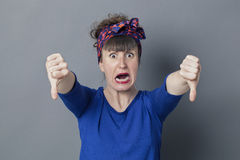 Scared young woman with thumbs down in foreground screaming Royalty Free Stock Photography