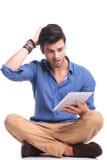 Scared zufällige Mannlesenachrichten auf seiner Tablette schauend Stockfoto