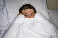 scareed man in bed royalty free stock image