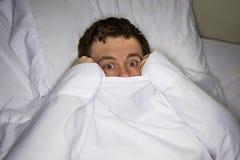 scareed Mann im Bett lizenzfreies stockbild