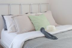 Scarf and white hat setting on stripe blanket with pastel color pillows.  royalty free stock images