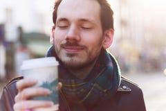 Scarfed man enjoying warm beverage Royalty Free Stock Image