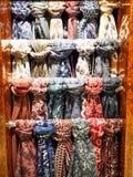 Scarfes brilhantes coloridos do pescoço no gancho em uma loja fotos de stock