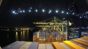 Scaricando i contenitori da un trasporto spediscono con le gru automatiche nel lasso di tempo 4k, notte nel porto del porto, stock footage