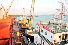Scarico della nave nel porto di Saigon, il Vietnam, il Mekong Viste degli ancoraggi, delle sponde del fiume e delle navi, rimorch fotografia stock