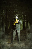 Scaring maniac with chainsaw. In the woods . Halloween and horror concept stock image