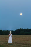 Scaring young woman wearing white dress with horse skull on her head at night field. With full moon Stock Images