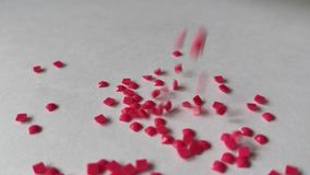 Scarlet diamond mosaic pours on the white surface of the background. Slow motion stock video footage