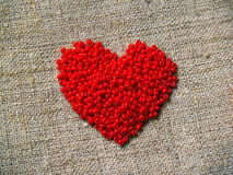 Scarlet heart. Valentine's heart from bright scarlet glass beads Stock Images