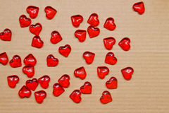 Scarlet hearts on carton background Stock Photos