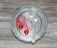 Scarlet hearts. Two vintage fork and two scarlet hearts on an empty pink plate Stock Photos