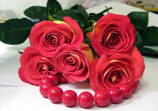 Scarlet roses. On large red beads Royalty Free Stock Photo