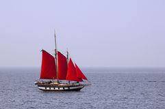 Scarlet sails. Sailing vessel with scarlet sails on a background of the dark blue sea and the sky royalty free stock photos