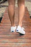 Scarpa da tennis bianca di usura di donna e camminare sul ponte di legno fotografie stock libere da diritti