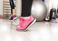 Scarpa da tennis della giovane donna che allunga gamba in palestra, concetto di sport clos Fotografia Stock Libera da Diritti