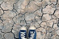 Scarpa da tennis sulla terra asciutta della crepa Immagini Stock Libere da Diritti