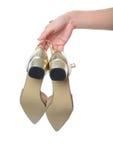 Scarpa dei tacchi alti dell'oro del vestito dalla tenuta della mano della donna immagini stock