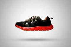 Scarpa pareggiante di sport neri & rossi isolata su fondo bianco Immagini Stock