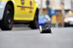 Scarpa sulla via con le automobili nel fondo dopo l'incidente Immagine Stock