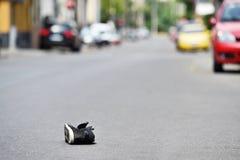 Scarpa sulla via con le automobili nel fondo dopo l'incidente Immagine Stock Libera da Diritti
