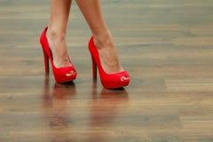 Scarpe appuntite dei tacchi alti rossi sulle gambe femminili Fotografia Stock Libera da Diritti