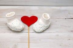 Scarpe bianche dei bambini su un fondo di legno bianco e su un cuore rosso Fotografie Stock